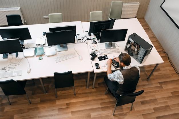 Widok z góry na otwartą przestrzeń biurową z mechanikiem. inżynier przygotowujący miejsce do pracy, naprawiający zepsuty komputer. naprawa, rozwój, koncepcja biznesowa