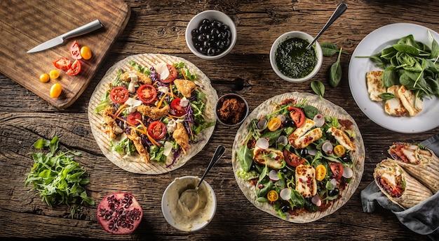 Widok z góry na otwarte tortille z warzywami i paskami kurczaka lub serem haloumi na rustykalnym stole.