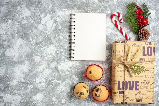 Widok z góry na otwarty notatnik i piękny świąteczny prezent z napisem miłosnym małe babeczki i gałęzie jodły akcesoria do dekoracji szyszek iglasty na powierzchni lodu