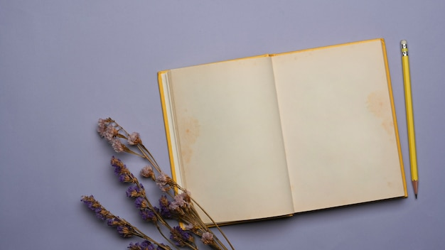 Widok z góry na otwarty notatnik, ołówek i suszony kwiat na fioletowym tle
