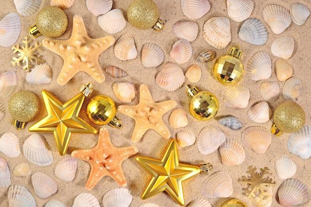 Widok z góry na ozdoby świąteczne, muszle i rozgwiazdy na piasku na plaży