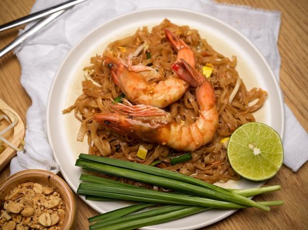 Widok z góry na pad thai, tajski makaron z mieszaniem i krewetkami, podawany z limonką, kiełkami fasoli i szczypiorkiem na stole w jadalni, tradycyjne tajskie jedzenie