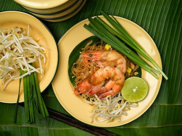 Widok z góry na pad thai, tajski makaron z mieszaniem i krewetkami, podawany z limonką, kiełkami fasoli i szczypiorkiem na tradycyjnym tajskim talerzu na liściach bananowca