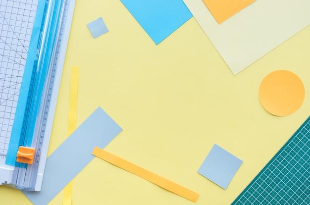 Widok z góry na papier cięty za pomocą narzędzia na kolorowym tle