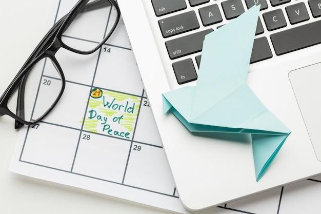 Widok z góry na papierową gołąbkę z laptopem i światowym dniem pokoju