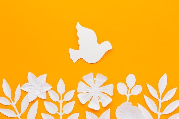 Widok z góry na papierową gołębicę i kwiaty