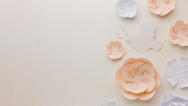 Widok z góry na papierową gołębicę z papierowymi kwiatami