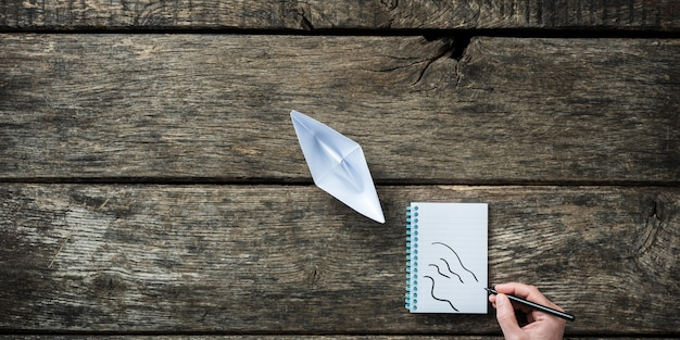 Widok z góry na papierową łódź origami z męską ręką rysującą fale wody w notatniku za nim.