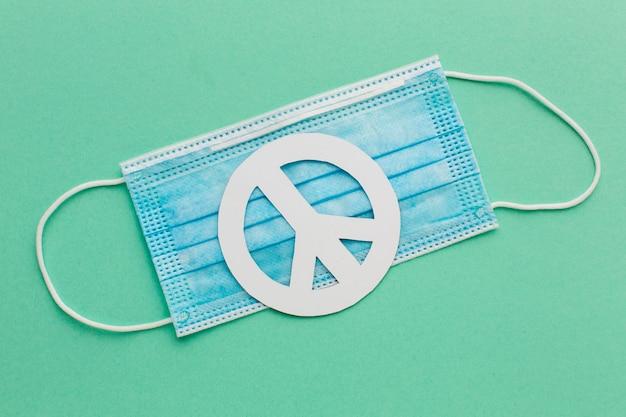 Widok z góry na papierowy znak pokoju z maską medyczną