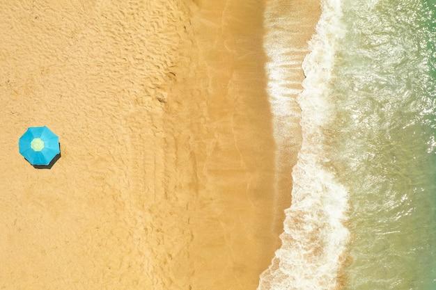 Widok z góry na parasol na złocistej, piaszczystej plaży obmywanej przez fale morza śródziemnego
