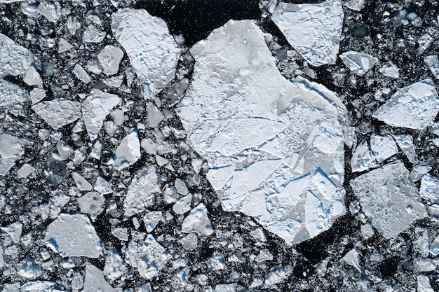 Widok z góry na pęknięty lód unoszący się w ciemnej wodzie