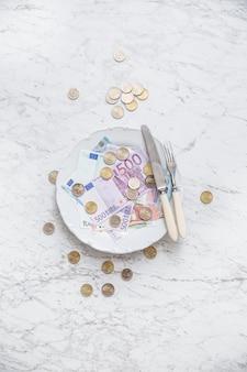 Widok z góry na pełny talerz monet i banknotów euro.