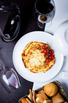 Widok z góry na pieczone naczynie pokryte roztopionym serem przyozdobionym z pomidorkami cherry