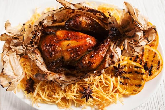 Widok z góry na pieczonego kurczaka ze smażonymi ziemniakami, podanego w papierze piekarniczym i grillowanych plasterkach cytryny