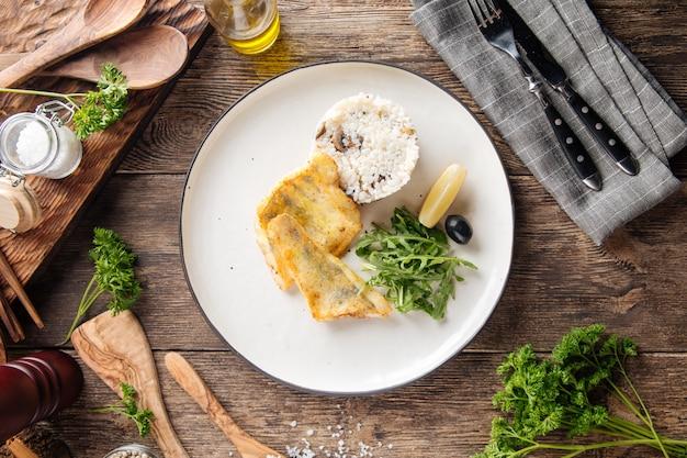 Widok z góry na pieczony filet z białej ryby z ryżem i rukolą