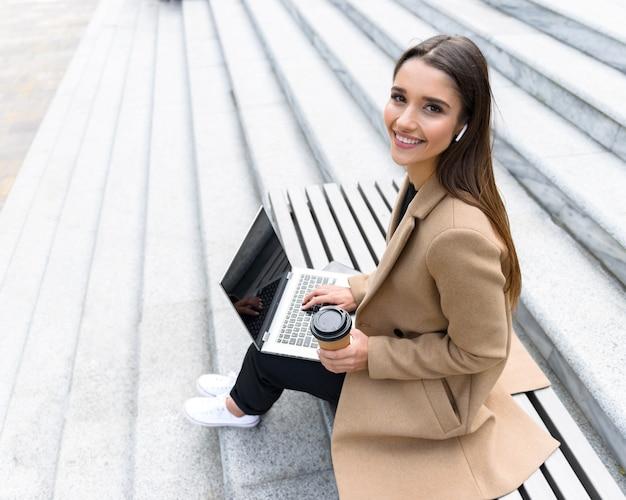 Widok z góry na piękną młodą kobietę ubraną w jesienny płaszcz, korzystający z laptopa siedzącego na ławce i pijącego filiżankę kawy na wynos