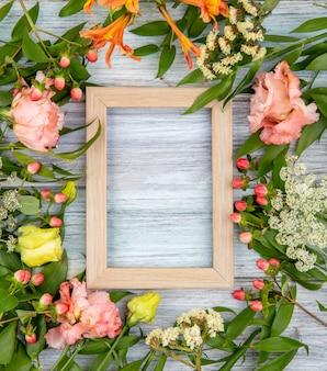 Widok z góry na piękne i kolorowe kwiaty z liśćmi na szarym drewnie z miejscem na kopię