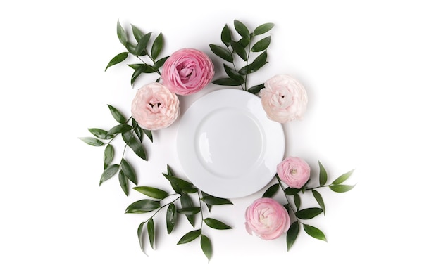Widok z góry na piękne nakrycie stołu z kwiatami i białym talerzem
