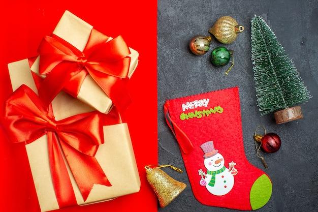Widok z góry na piękne prezenty ze wstążką w kształcie kokardki obok gałęzi jodłowych ozdobnych skarpet świątecznych na czerwonym tle