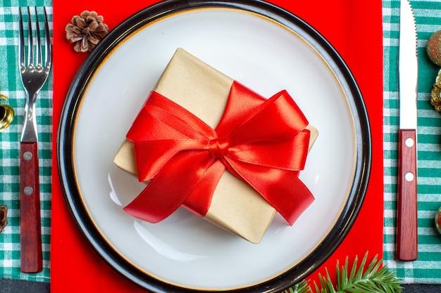 Widok z góry na piękne pudełko z czerwoną wstążką w kształcie kokardki na talerzu i zestaw sztućców na zielonym ręczniku w paski
