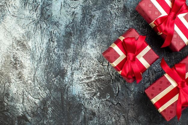 Widok z góry na pięknie zapakowane pudełka na prezenty po lewej stronie na ciemnym