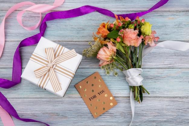 Widok z góry na piękny i kolorowy bukiet kwiatów przewiązanych białą wstążką na szarym drewnie