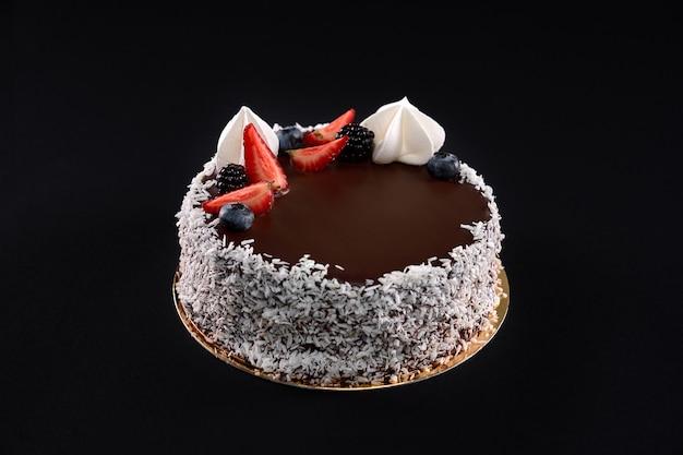 Widok z góry na piękny, smaczny brązowy tort ozdobiony wiórkami kokosowymi na bokach, świeżymi jagodami i białym kremem. pyszny deser z polewą czekoladową na białym tle na czarnym tle.