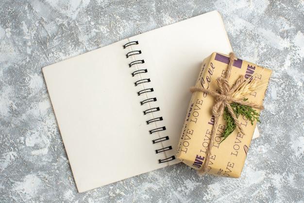 Widok z góry na piękny świąteczny prezent z napisem miłości na otwartym notatniku na lodowym stole