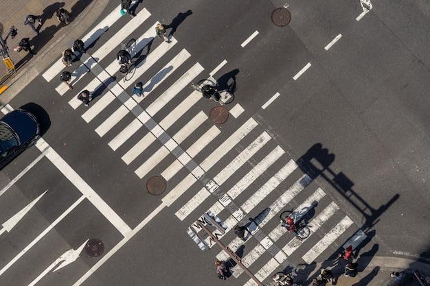 Widok z góry na pieszych tłum niezdefiniowanych ludzi idących wiaduktem skrzyżowania ulic