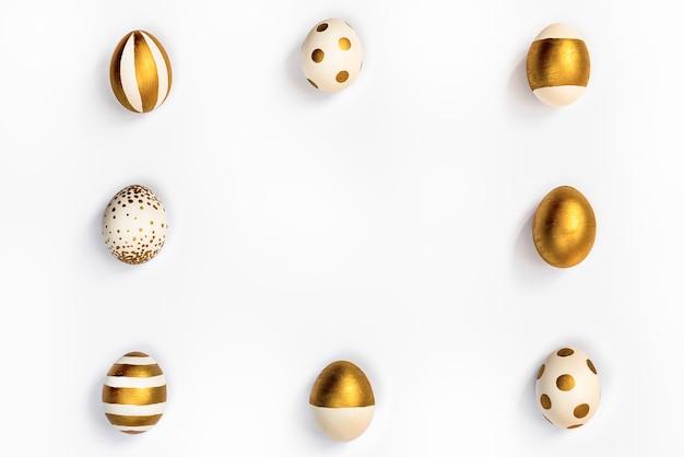 Widok z góry na pisanki zabarwione złotą farbą ułożone w kwadrat. białe tło. skopiuj miejsce.