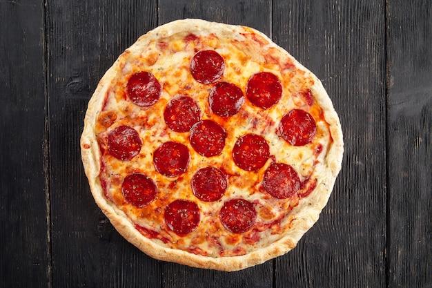 Widok z góry na pizzę pepeproni na drewnianym biurku