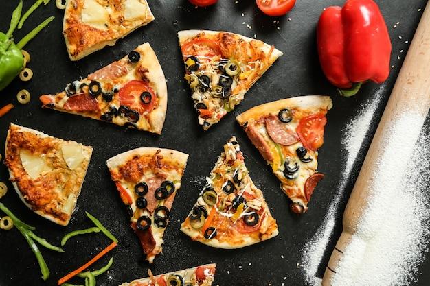 Widok z góry na pizzę z pomidorami, oliwkami i papryką na czarnym stole