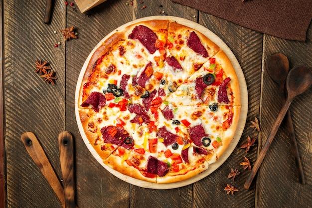 Widok z góry na pizzę z wędzoną wołowiną i warzywami na drewnianym stole