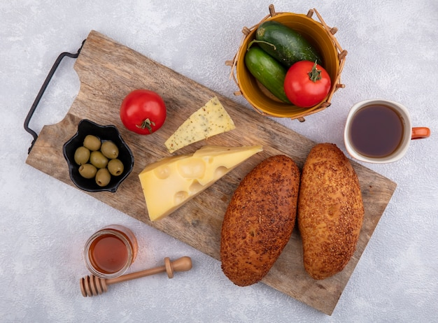 Widok z góry na placki sezamowe na drewnianej desce kuchennej z zielonymi oliwkami na czarnej misce z serem i miską ogórków i pomidorów na białym tle
