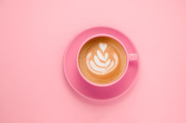 Widok z góry na płaską kawę z różową filiżanką latte art na delikatnym pastelowym różu