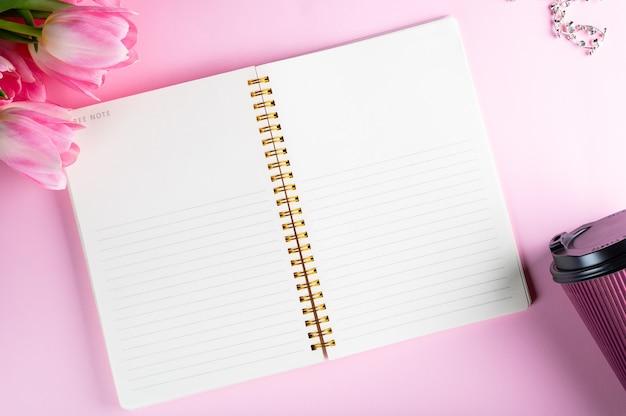 Widok z góry na płasko leżał pusty notes z kwiatami. makieta. przestrzeń tekstowa. kobiety płasko. flatlay na dzień kobiet. bizneswoman flatlay. pusty notatnik.