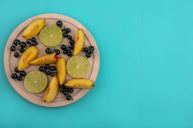 Widok z góry na plasterki brzoskwini z plasterkami czarnej porzeczki i limonki na drewnianej tacy na niebieskiej powierzchni
