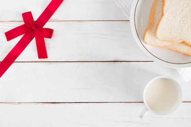 Widok z góry na plasterki chleba na talerzu z gorącym mlekiem w białym kubku i rogu mają wstążkę na białym stole z drewna, śniadanie rano, świeże domowe, miejsce na kopię