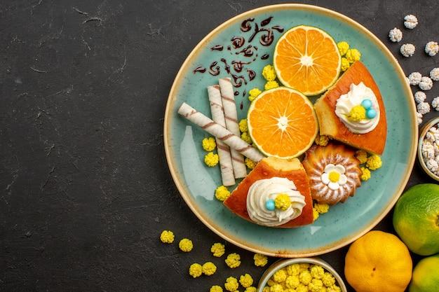Widok z góry na plasterki ciasta z pokrojonymi świeżymi mandarynkami i cukierkami na ciemnym biurku