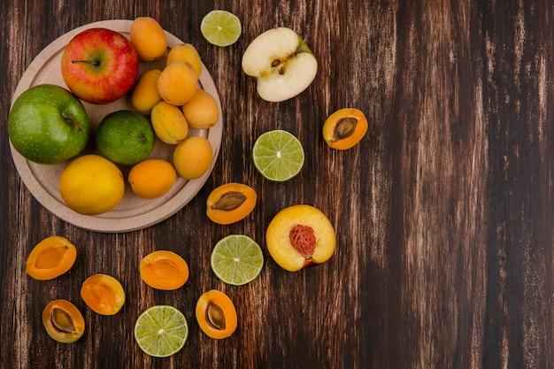 Widok z góry na plasterki limonki z morelami brzoskwiniowymi i jabłkiem na powierzchni drewnianych
