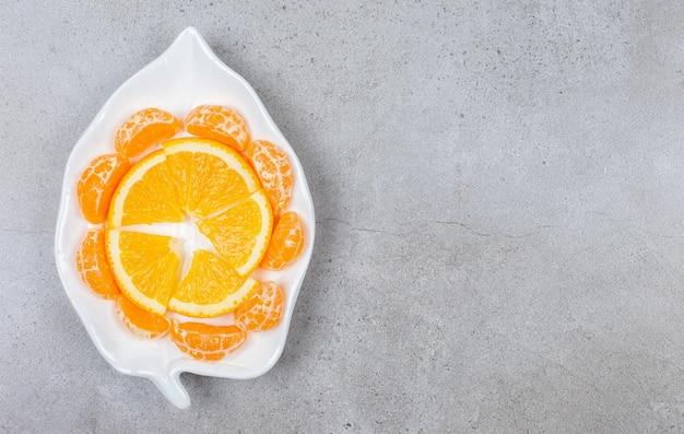 Widok z góry na plasterki mandarynki wokół plasterka pomarańczy