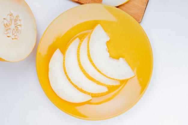 Widok z góry na plasterki melona na talerzu i wyciąć jeden na białym tle