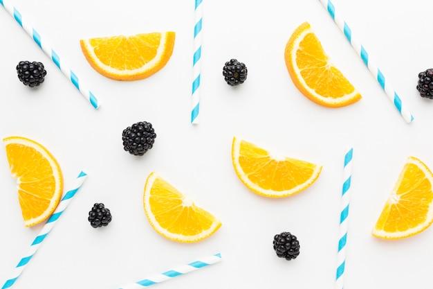 Widok z góry na plasterki pomarańczy i jeżyny ze słomkami na sok