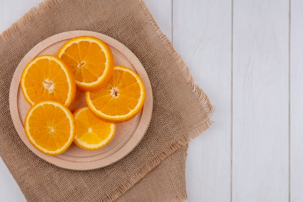 Widok z góry na plasterki pomarańczy na stojaku na beżowej serwetce na białej powierzchni