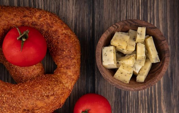 Widok z góry na plasterki sera na drewnianej misce z pomidorami na drewnianym tle