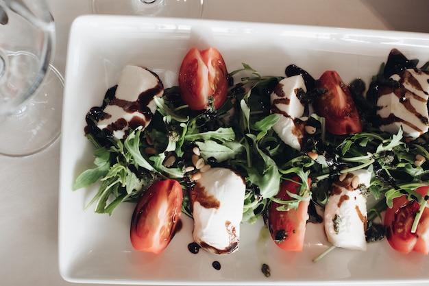 Widok z góry na plasterki świeżych pomidorów, pietruszki i serka mascarpone polane sosem balsamicznym.