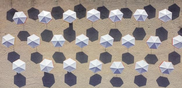 Widok z góry na plażę z białymi parasolami.