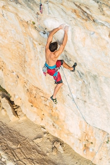 Widok z góry na plecy mężczyzny wspinającego się na formację skalną