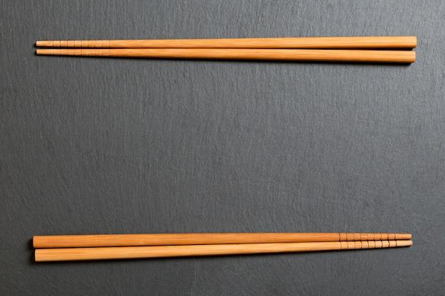 Widok z góry na płytce czarny łupek z drewnianymi pałeczkami na ciemnym