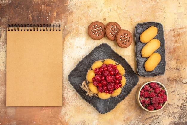 Widok z góry na podarunkowy tort i ciastka na brązowych talerzach z owocami i notatnik na stole mieszanym